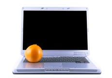 Computadora portátil y naranja Foto de archivo