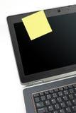 Computadora portátil y nota pegajosa del amarillo Imagen de archivo