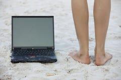 Computadora portátil y piernas en la playa Fotos de archivo libres de regalías