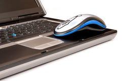 Computadora portátil y ratón Foto de archivo libre de regalías
