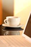 Computadora portátil y taza de té Foto de archivo libre de regalías
