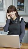 Computadora portátil y teléfono de la mujer Foto de archivo