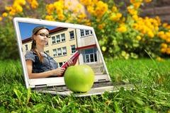 Computadora portátil con el estudiante femenino en la pantalla Fotos de archivo libres de regalías