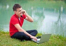 Computadora portátil del móvil del hombre joven Foto de archivo libre de regalías