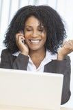 Computadora portátil del teléfono celular de la empresaria de la mujer del afroamericano Fotografía de archivo