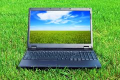 Computadora portátil en hierba Fotos de archivo