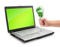 Computadora portátil y dinero Imágenes de archivo libres de regalías