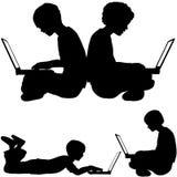Computadoras portátiles del uso del muchacho de IRL que sientan la mentira en la tierra Foto de archivo