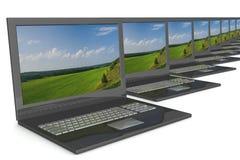 Computadoras portátiles abiertas de la fila con un paisaje. Fotos de archivo