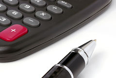 Computation. Closeup of a calculator which lies next to a ballpoint pen Stock Photography