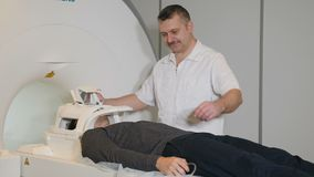 Computed tomography concept. Health concept. Male Person gets scanned by magnetic resonance imaging scanner in modern. Hospital. Male radiology doctor in white stock footage