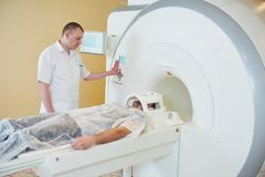 MRI scan test or computed tomography in hospital. Computed tomography or MRI scan test. Male radiologist men preparing patient for CT scanning Stock Photography