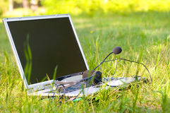 Computer. With headphones and a microphone, on a green lawn in the summer Stock Image