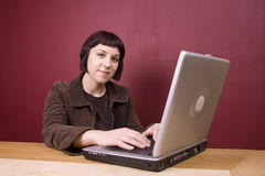 On Computer. Young woman using a laptop in a home environment Royalty Free Stock Photography