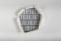 Computer access. A piece of torn white paper over a computer keyboard with a hole revealing the keys Stock Image