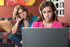 Computer addicted girl ignores her worried mother Royalty Free Stock Image