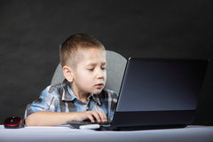 Computer addiction child with laptop notebook Stock Photos