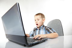Computer addiction emotional boy with laptop. Computer addiction emotional child boy with laptop notebook playing games isolated on white background Royalty Free Stock Photos