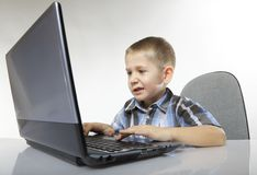 Computer addiction emotional boy with laptop. Computer addiction emotional child boy with laptop notebook playing games isolated on white background Royalty Free Stock Image