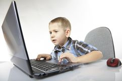 Computer addiction emotional boy with laptop. Computer addiction emotional child boy with laptop notebook playing games  on white background Stock Photo