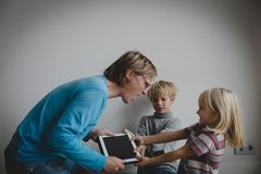 Computer addiction- father taking touch pad from angry kids. Kids computer addiction- father taking pad from angry son and daughter stock photo