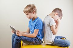 Compuer addiction. One boy using tablet and other kid rubbing tired eyes after long time playing game. Computer addiction. One boy using tablet and other kid royalty free stock image