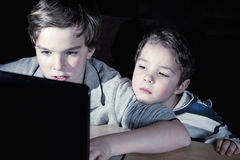 Computer addiction. Two brothers playing computer games late in the evening Royalty Free Stock Image
