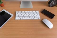 Computer alle in einem, intelligentes Telefon, Tablette, Betriebsvase, Kaktus, Bleistifte und Uhr stockfoto