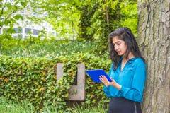 Computer americano della compressa della lettura dello studente di college dell'indiano orientale fuori Fotografie Stock