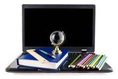 Computer, Bücher, Bleistifte und eine Kugel Lizenzfreies Stockbild