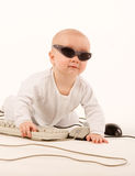 Computer baby. Baby in sun glasses playing with computer Stock Images