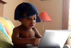 Computer Baby. Baby focusing with Computer on bed Stock Images