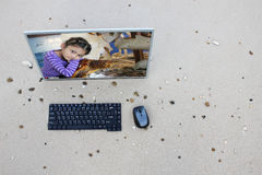 Computer on the beach with Asian girl and sea turtles on the screen. Royalty Free Stock Images