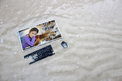 Computer on the beach with Asian girl and sea turtles on the screen. Stock Photography