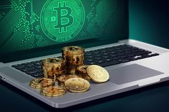 Computer with Bitcoin symbol on-screen and piles of golden Bitcoin Stock Photos