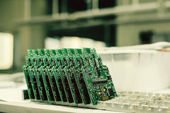 Computer boards stand in a row at the factory for the production of spare parts. Stock Photography