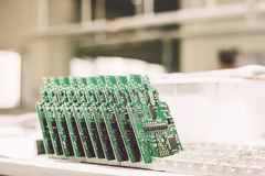Computer boards stand in a row at the factory for the production of spare parts. Stock Images