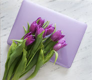 Computer with bouquet of purple tulips Royalty Free Stock Image