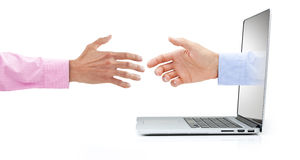 Computer Business Marketing Handshake. A businessman reaching out of a laptop computer to shake hands on a white background Stock Photos