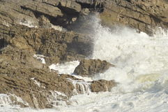 Waves breaking over rocks on the Gower peninsula, Swansea, Wales, U.K., during a winter storms Royalty Free Stock Photography