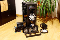 Computer case water cooling fans pump reservoir. Disassembled computer case with fans, custom water cooling, pump, reservoir and power supply unit, placed on the stock image