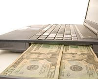 Computer cash. A laptop computer with money coming out of it on white Royalty Free Stock Photo