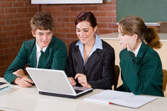 Computer class. Female high school teacher teaching computer class to her students Stock Photography