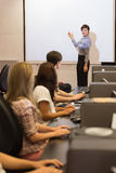 Computer class looking at teacher pointing on projection screen Royalty Free Stock Images