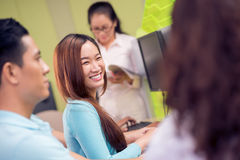In the computer classroom. Image of a laughing student at the lesson of informatics on the foreground Stock Photos