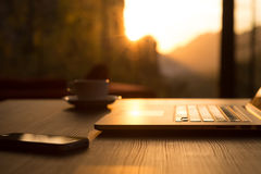 Computer Coffee Mug and Telephone on black wood table sun rising. Nomad Work Concept Image Computer Coffee Mug and Telephone on black wood Table and Evening Stock Photos