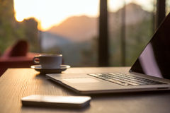 Computer Coffee Mug and Telephone on black wood table sun rising Royalty Free Stock Photography