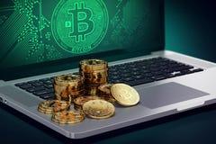 Computer con il simbolo di Bitcoin sullo schermo ed i mucchi di Bitcoin dorato Fotografie Stock