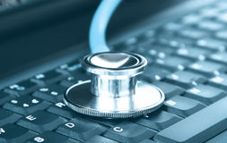Computer concept of a stethoscope closeup on a computer keyboard. Technical support concept of a stethoscope closeup on a computer keyboard in blue tone Stock Photography