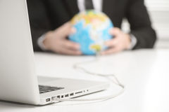 Computer connected to earth globe Stock Photography